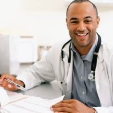 Male doctor looking at medical chart, smiling, portrait